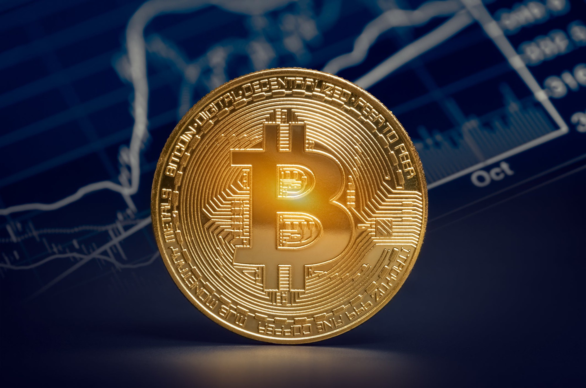 A physical gold bitcoin stood in front of a digital chart with visible price and volume metrics.